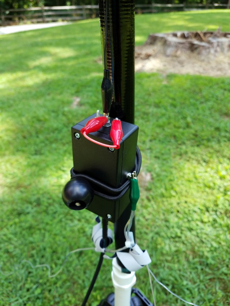 The matching network is attached to the pole with a small bungee cord. In this picture, the red jumpers are configured for the 30M band.