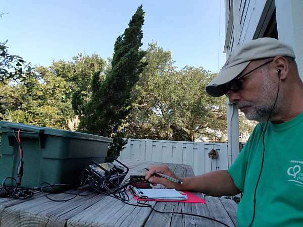 Operating from the picnic table. Above my arm, in the background, you can see the feedpoint for the inverted L antenna. My 9:1 UNUN is wrapped up for weather protection.